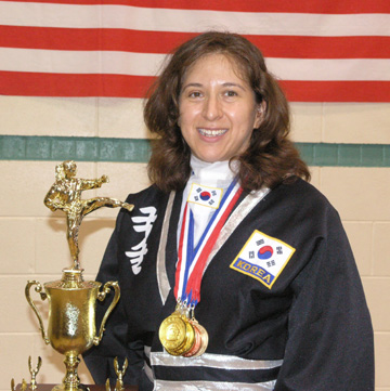 Photo of JKN Yvonne Jarique holding trophy and wearing medals.